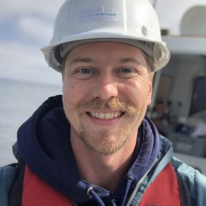 Scientist on boat with hardhat